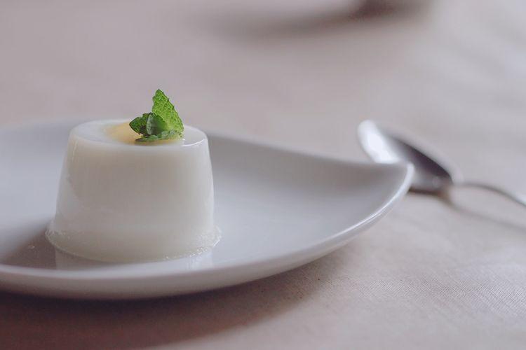 Ilustrasi puding putih di atas piring.