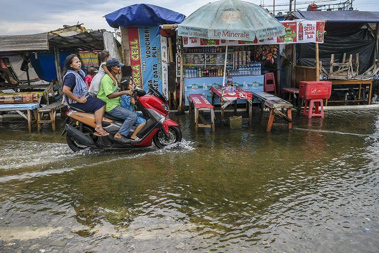 Warga menaiki motor melintasi banjir rob di Pelabuhan Kali Adem, Muara Angke, Jakarta, Jumat (1/1/2021). Banjir yang terjadi sejak Kamis (31/12/2020) itu dikarenakan pasang surut air laut.
