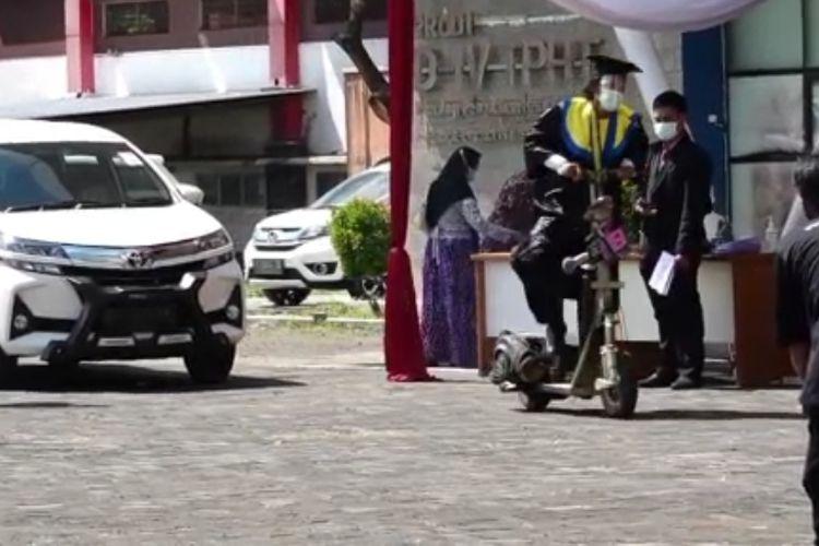 Wisudawan bernama M. Andika Maulana Putra mengendarai vespa tua saat wisuda drive thru di Poltek Negeri Banyuwangi, Sabtu (12/6/2021).