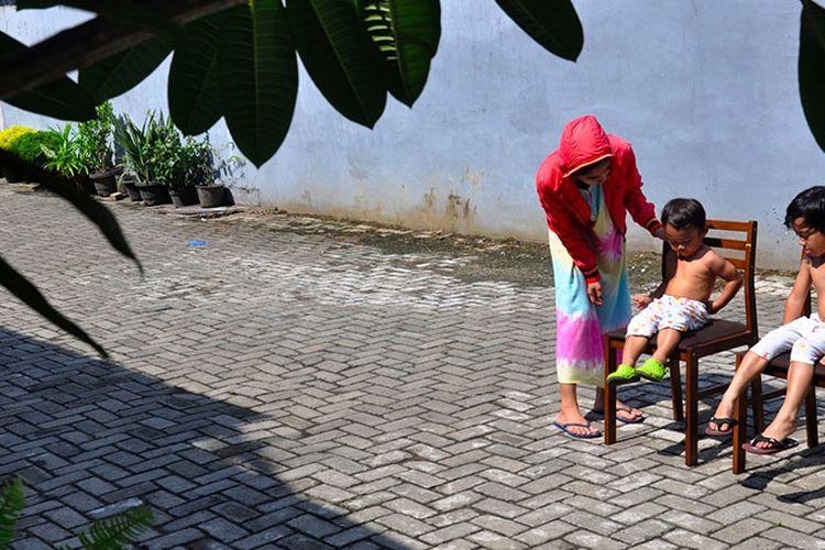Seorang ibu menjemur kedua anaknya di bawah sinar matahari saat Self Isolation atau tinggal di rumah di Medan, Sumatera Utara, Minggu (22/3/2020). Berjemur diri di bawah matahari di antara pukul 08.00 WIB-11.00 WIB merupakan salah satu upaya yang paling sederhana untuk menjaga kesehatan selama wabah virus COVID-19.