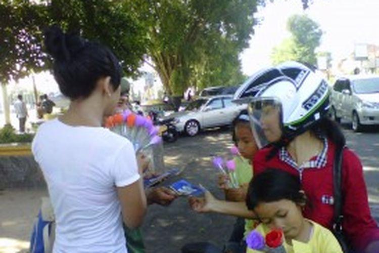 Salah seorang anggota komunitas Be Positif membagi-bagikan bunga dan stiker anti narkoba di kawasan alun-alun Kota Magelang, Rabu (26/6/2013).