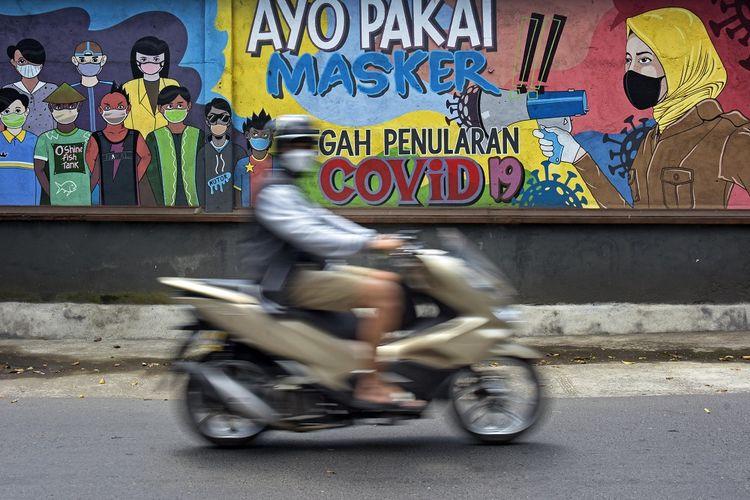 Pengendara sepeda motor melintas dekat mural bertemakan disiplin bermasker untuk pencegahan penularan COVID-19 di Mataram, NTB, Minggu (29/8/2021). ANTARA FOTO/Ahmad Subaidi/rwa.