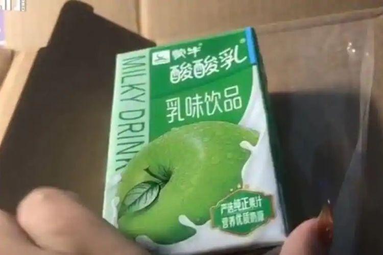 Liu, seorang perempuan asal Anhui, China, menunjukkan minuman yogurt rasa apel yang dia terima dari kotak yang seharusnya berisi iPhone 12 Pro Max.
