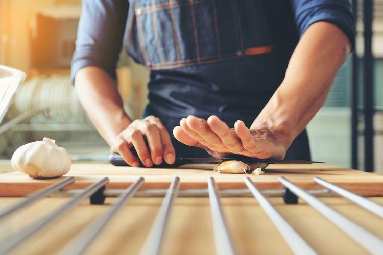 Ilustrasi mengupas bawang putih menggunakan sisi pisau.