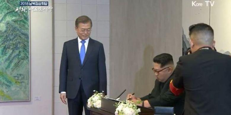 Inilah momen di mana Pemimpin Korea Utara Kim Jong Un menuliskan pesan di buku tamu disaksikan Presiden Korea Selatan Moon Jae In dalam Konferensi Tingkat Tinggi Antar-Korea di Panmunjom, Jumat (27/4/2018).