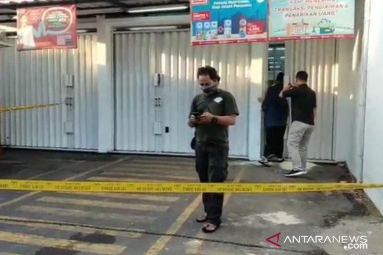 Polisi berseragam bebas dari Polsek Duren Sawit, Jakarta Timur, memasang garis polisi di lokasi kejadian perampokan minimarket, Kamis (16/4/2020) dini hari.