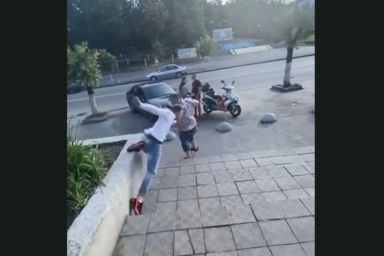 Tangkapan layar memperlihatkan seorang pria di Ukraina terpeleset ketika berusaha menendang lelaki di depannya. Pria berbaju putih itu dihajar menggunakan sosis setelah diketahui tidak mengenakan masker di supermarket.