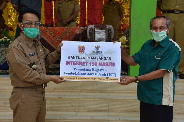 Bupati Indra Catri menyerahkan paket wifi gratis kepada.masjid dan sekolah di Agam untuk membantu siswa yang belajar online