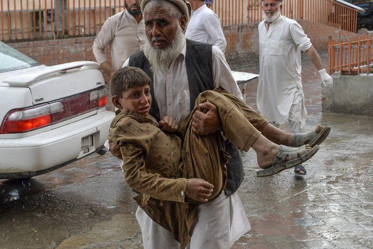 Warga menggotong seorang remaja yang terluka akibat ledakan di sebuah masjid di distrik Haska Mina, sekitar 50 kilometer dari Jalalabad, ibu kota provinsi Nangarhar, pada Jumat (18/10/2019).