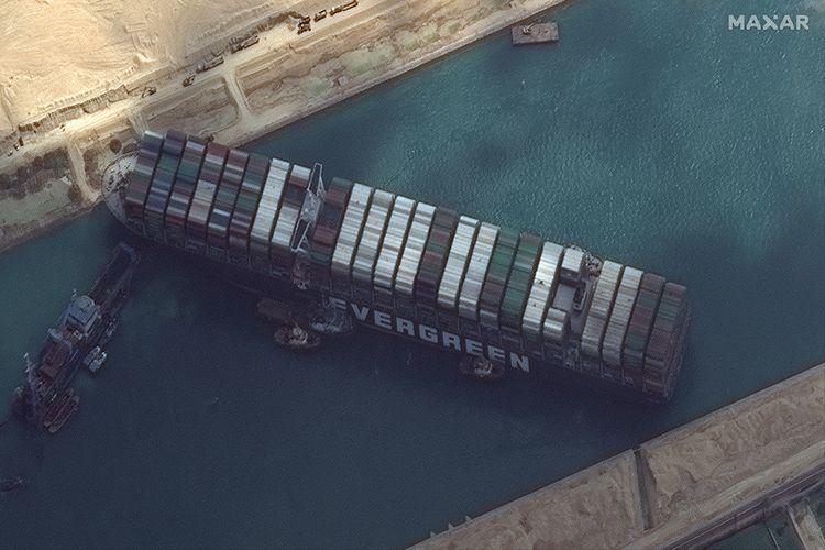 Foto satelit dari Maxar Technologies memperlihatkan kapal kargo MV Ever Given masih terjebak diagonal di Terusan Suez, dekat Suez, Mesir, pada Jumat (26/3/2021). Akibat Terusan Suez macet, lebih dari 200 kapal antre masuk dan beberapa di antaranya mulai berputar mengubah rute.
