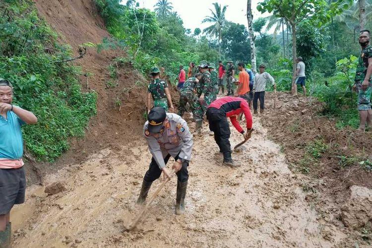 BUKA JALAN—Anggota Polri, TNI, BPBD dan relawan bahu membahu membersihkan tumpukan tanah longsor yang menutup ruas jalan di Desa Kepel, Kecamatan Kare, Kabupaten Madiun, Senin (15/2/2021).
