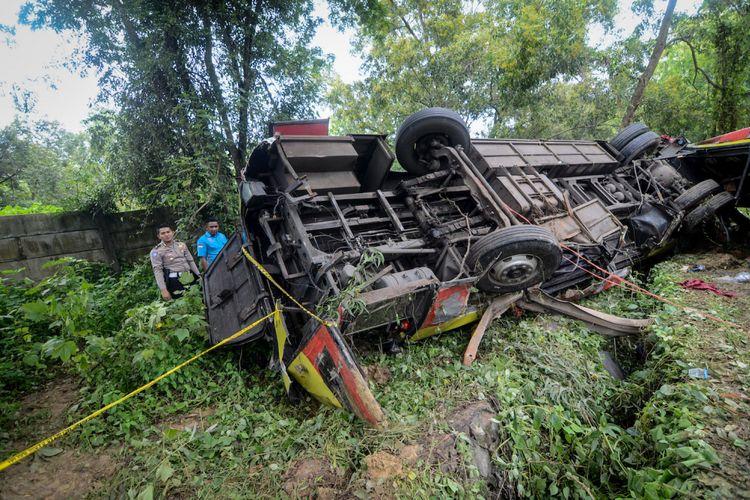 Polisi memeriksa bus Arimbi jurusan Bandung-Merak yang mengalami kecelakaan di kilometer 70+400 Jalan Tol Purwakarta-Bandung-Cileunyi (Purbaleunyi), Kabupaten Purwakarta, Jawa Barat, Senin (28/1/2019). Dalam kecelakaan tersebut setidaknya tujuh orang meninggal dunia.