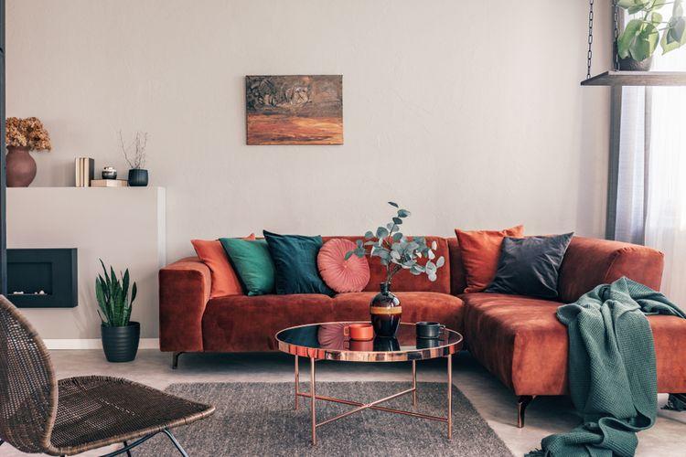 Ilustrasi dekorasi ruang tamu dengan warna merah marun dan abu-abu.
