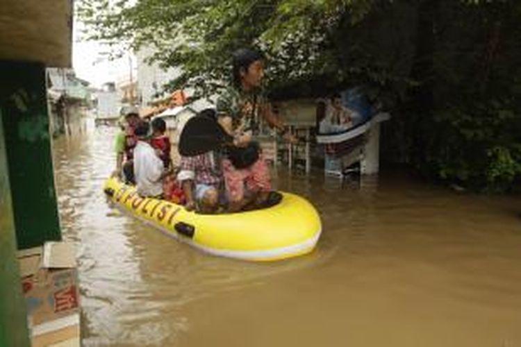 Warga diungsikan menggunakan perahu karet dari banjir yang melanda kawasan Bidara Cina, Jakarta, Senin (13/1/2014). Hujan yang melanda Jakarta sejak Minggu pagi ditambah meluapnya sungai Ciliwung akibat banjir kiriman dari Bogor mengakibatkan sejumlah kawasan ini terendam banjir sejak Minggu malam. KOMPAS IMAGES/RODERICK ADRIAN MOZES
