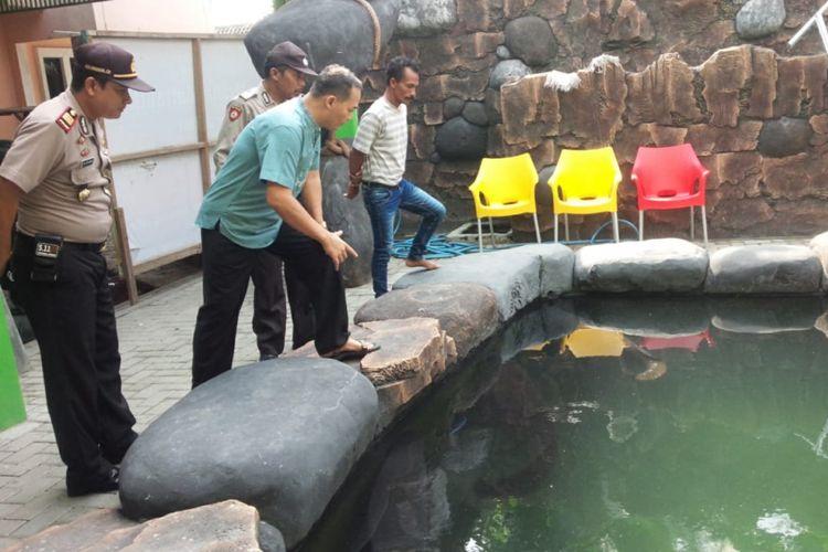 Masudin (baju biru), pemilik ikan Arapaima di Jombang, Jawa Timur, ketika menerima polisi yang datang mengecek.