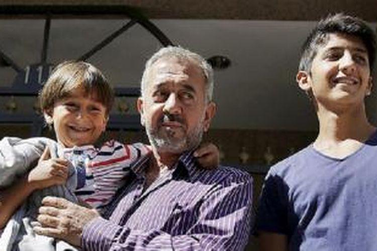 Osama Abdul Mohsen (tengah), migran asal Suriah, bersama dua putranya, Zaid dan Mohammed al-Ghadabe (kanan), di depan rumah baru mereka di Getafe, Spanyol, Kamis (17/9). Mohsen ditawari jabatan pelatih di sekolah sepak bola Getafe setelah terekam kamera terjatuh bersama Zaid karena disandung perempuan juru kamera saat melarikan diri dari kejaran polisi di Hongaria.