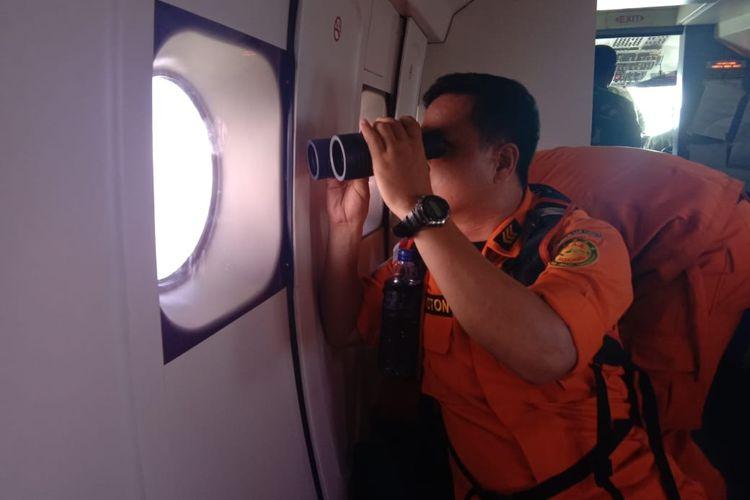 Seorang personel SAR tengah memantau perairan dari pesawat udara patroli maritim U-6212 milik TNI AL, Senin (13/5/2019)