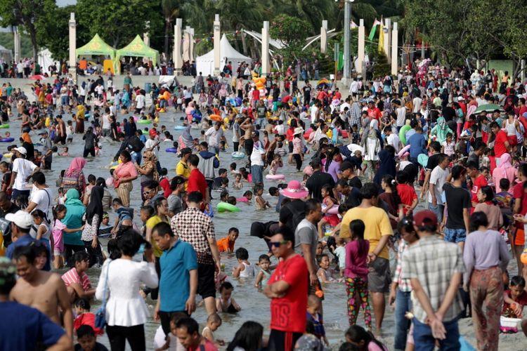 Pengunjung memanfaatkan liburan mengunjungi pantai di kawasan Taman Impian Jaya Ancol, Jakarta, Selasa (27/6/2017). Sejumlah lokasi wisata di Jakarta padat pengunjung pada libur lebaran.