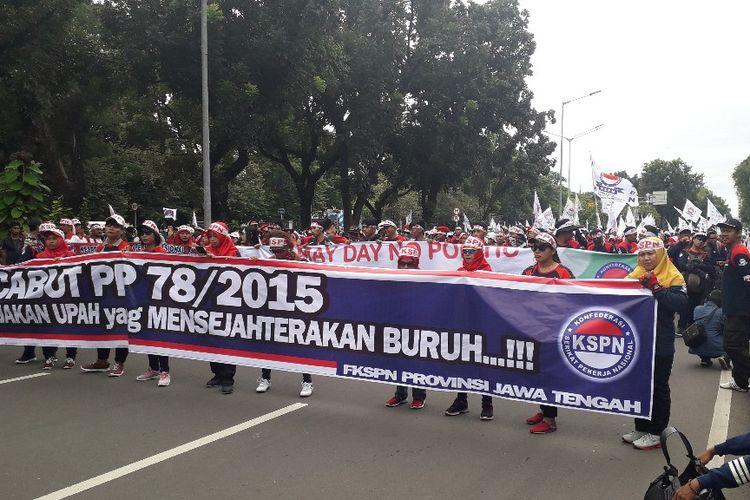 Massa peserta aksi Hari Buruh Internasional berunjuk rasa di Jalan Medan Merdeka Selatan dekat Monumen Nasional, Rabu (1/5/2019).