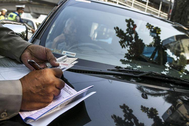 Petugas kepolisian menilang mobil berplat nomor genap yang memasuki Jalan Salemba Raya, di Matraman, Jakarta, Senin (9/9/2019). Petugas kepolisian mulai memberlakukan penindakan berupa tilang terhadap pengendara mobil yang melanggar di kawasan perluasan sistem ganjil-genap.