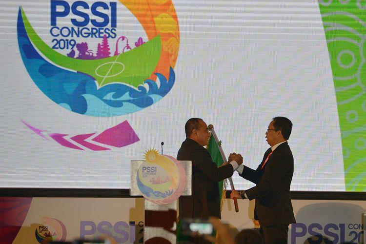 Ketua Umum PSSI Edy Rahmayadi (kiri) berjabat tangan saat menyerahkan bendera organisasi sepak bola Indonesia kepada Wakil Ketua Umum PSSI Djoko Driyono setelah menyatakan pengunduran diri dalam pembukaan Kongres PSSI 2019 di Nusa Dua, Bali, Minggu (20/1/2019). Djoko Driyono resmi menjabat Ketua Umum PSSI.