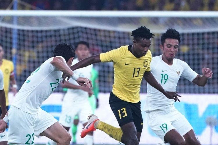 Mohamadou Sumareh (tengah) berduel dengan Bayu Gatra (kanan) dan Gavin Kwan Adsit  pada laga Malaysia Vs Indonesia dalam lanjutan Kualifikasi Piala Dunia 2022 Grup G di Stadion Nasional Bukit Jalil, Selasa 19 November 2019,