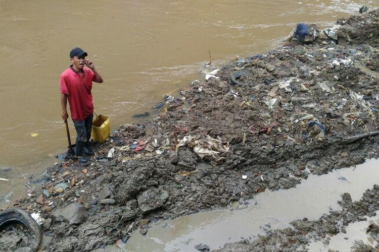 Seorang warga berdiri di atas timbunan lumpur Kali Krukut.