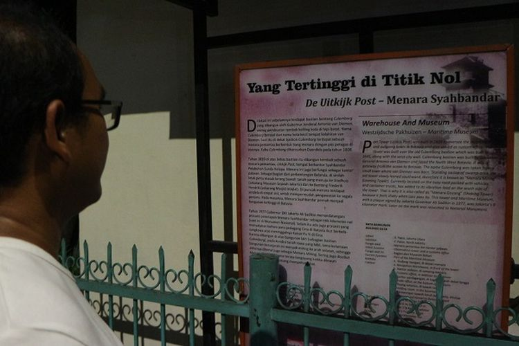 Peserta tur melihat papan deskripsi tentang Menara Syahbandar dalam acara tur wisata malam museum bahari, Sabtu (28/12/2019).
