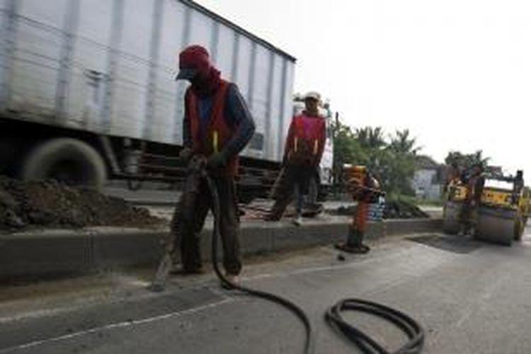 Para pekerja melakukan perbaikan jalur Pantai Utara (Pantura) di Jalan Ahmad Yani, Cikampek, Jawa Barat, Sabtu (27/7/2013). Rencananya proyek perbaikan ini akan rampung pada 10 hari sebelum Hari Raya Idul Fitri.