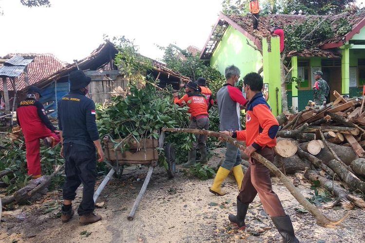 BERSIHKAN--Tim gabungan bersama warga membersihkan pohon tumbang yang menimpa gedung SD dan rumah warga Desa Jaten, Kecamatan Selogiri, Kabupaten Wonogiri, Jawa Tengah.