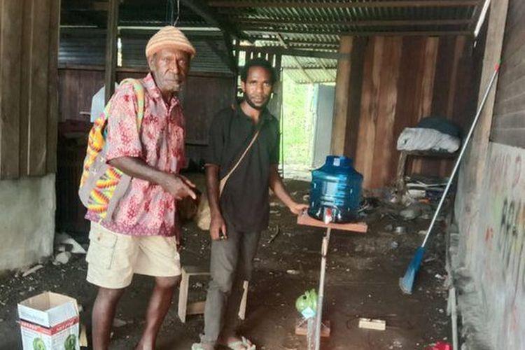Yason Agapa (kanan) berpose bersama pembeli kompor oli bekasnya.