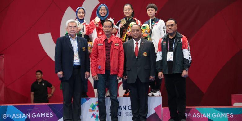Defia Rosmaniar berfoto di belakang Presiden Republik Indonesia, Joko Widodo, bersama Chef de Mission (CdM) Tim Indonesia, Komjen Pol. Syafruddin, seusai pengalungan medali emas taekwondo di JCC Plenary Hall, 19 Agustus 2018.
