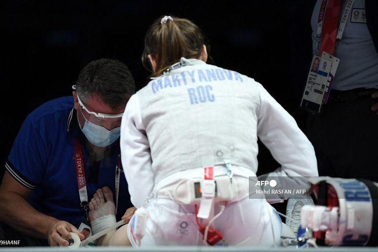 Atlet anggar Rusia Marta Martyanova menerima perawatan medis dalam final anggar Olimpiade Tokyo kelas foil melawan Perancis di Makuhari Messe Hall di Chiba City, Prefektur Chiba, Jepang, pada 29 Juli 2021.