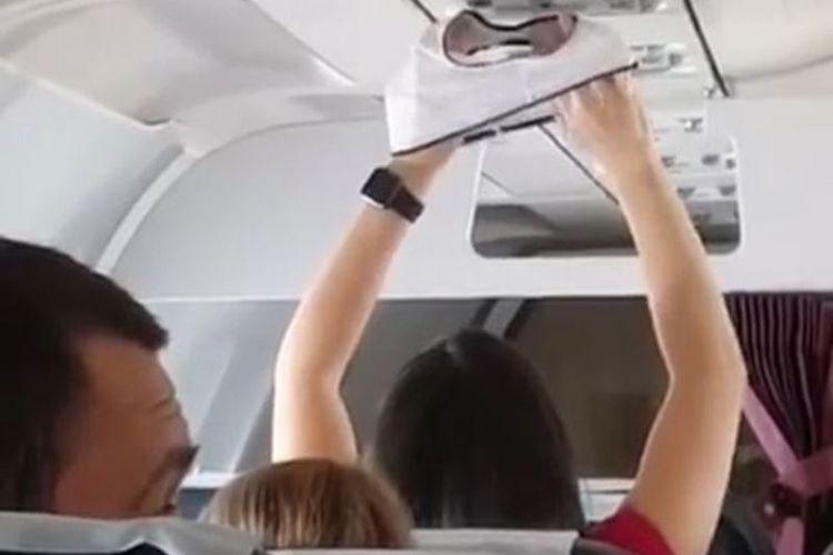 Dalam foto yang merupakan hasil tangkapan layar ini terlihat seorang perempuan mengangkat sepotong celana dalam untuk dikeringkan di bawah lubang ventilasi AC di dalam kabin penumpang.