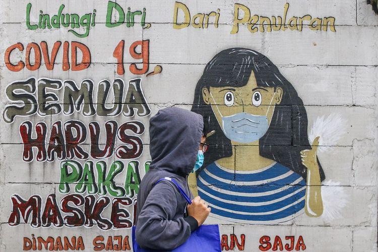 Warga melintas di dekat mural bertemakan COVID-19 di Petamburan, Jakarta, Rabu (21/7/2021). Berdasarkan data Kemenkes RI, pada hari pertama perpanjangan Pemeberlakuan Pembatasan Kegiatan Masyarakat (PPKM) kasus COVID-19 di Indonesia kembali menurun dari 38.325 orang menjadi 33.772 orang per hari. ANTARA FOTO/Rivan Awal Lingga/foc.