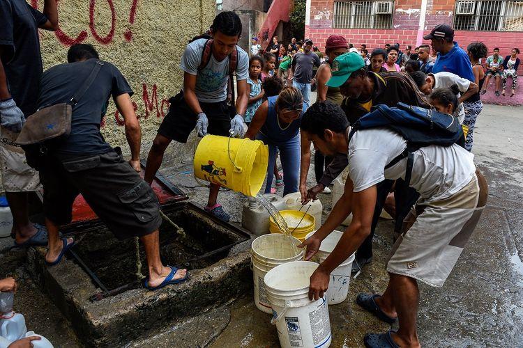 Warga mengisi tong mereka dengan air di kawasan Petare dekat Caracas pada 1 April 2019. Pemadaman listrik yang terjadi selama satu bulan terakhir membuat pasokan air ke rumah warga terputus.
