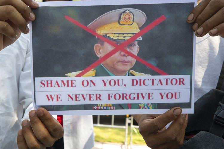 Warga negara Myanmar yang tinggal di Thailand memegang foto yang mengecam Panglima Tertinggi militer Myanmar Jenderal Min Aung Hlaing, selama protes di depan gedung PBB di Bangkok, Thailand, Rabu (3/2/2021).