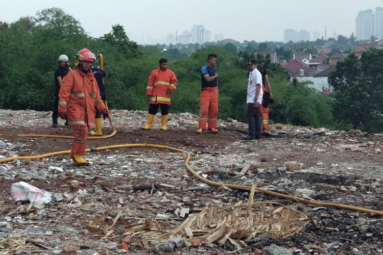 Pemadam kebakaran memadamkan asap yang muncul dari dalam tanah di Jalan Anggrek 1, Bintaro, Jakarta Selatan, Rabu (24/10/2018).