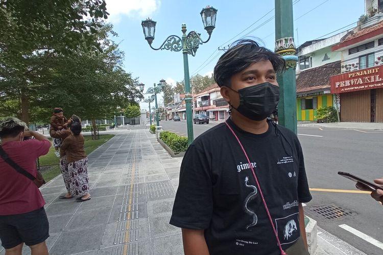 Habib (baju hitam) saat memotret wisatawan yang menggunakan jasanya, Rabu (1/9/2021)