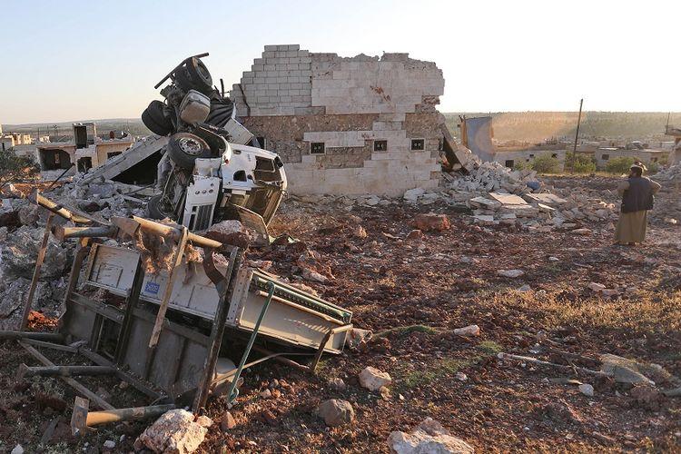 Seorang warga melihat reruntuhan bangunan dan kendaraan yang hancur akibat serangan udara Rusia di kota Kafranbel pada 20 Mei 2019.