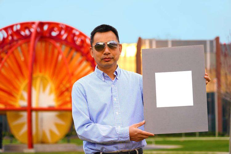 Professor Xiulin Ruan memegang sampel cat terputih di dunia.
