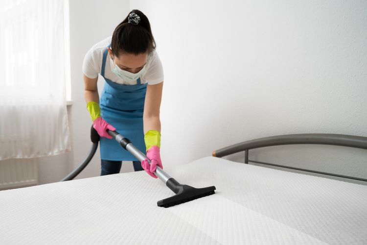 Ilustrasi membersihkan kasur dengan vacuum cleaner.