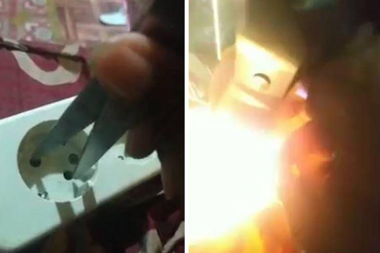 Tangkapan layar video yang menampilkan seseorang bersuara perempuan mencoba mencolokkan ujung gunting ke lubang stop kontak.