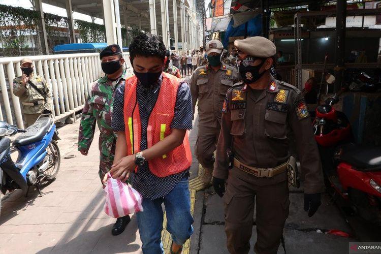 Pelanggar PSBB menerima sanksi memakai rompi oranye dan memungut sampah di kawasan Tanah Abang, Jakarta Pusat, Rabu (13/5/2020). (Sugiharto Purnama)
