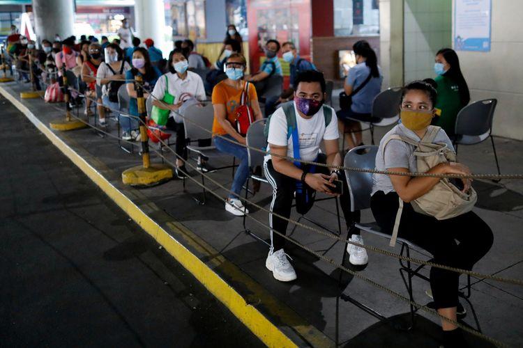 Para calon penumpang memakai masker untuk melindungi diri dari Covid-19, saat menanti kedatangan bus di Quezon City, Metro Manila, Filipina, 14 Juli 2020.