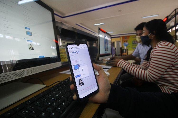 Petugas mendampingi warga yang melakukan pendaftaran calon peserta Kartu Prakerja di LTSA-UPT P2TK di Surabaya, Jawa Timur, Senin (13/4/2020).