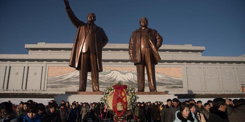 Orang-orang berjalan di depan patung pemimpin Korea Utara Kim Il Sung (kiri) dan Kim Jong Il (kanan), setelah meletakkan bunga untuk menandai ulang tahun keenam kematian Kim Jong Il, di bukit Mansu, Pyongyang, Minggu (17/11/2017). (AFP/Kim Won Jin)