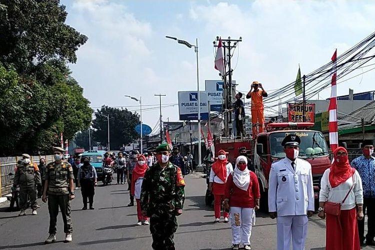 Berbagai unsur masyarakat mulai dari pihak RT, RW, Lembaga Musyawarah Kelurahan (LMK), Forum Kewaspadaan Dini Masyarakat (FKDM), Karang Taruna dan Pemberdayaan Kesejahteraan Keluarga (PKK), Pemadam Kebakaran (Damkar), Satpol PP, petugas Stasiun Lenteng Agung, petugas Penanganan Prasarana Sarana Umum (PPSU), TNI, dan warga menyanyikan lagu Indonesia Raya di Jalan Lenteng Agung, Jagakarsa, Jakarta, Senin (17/8/2020).