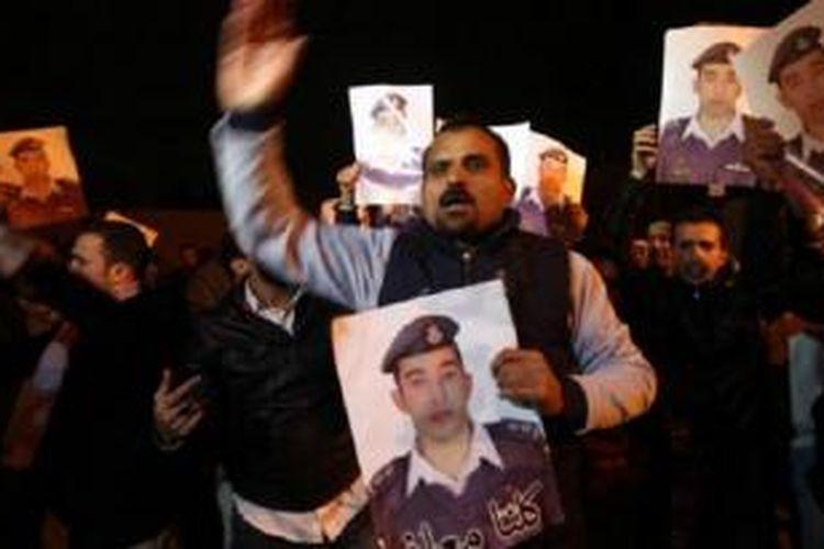Sanak keluarga pilot Muath al-Kasasbeh yang ditahan oleh ISIS melakukan protes di depan istana raja di Amman, Yordania, untuk menuntut pembebasannya.