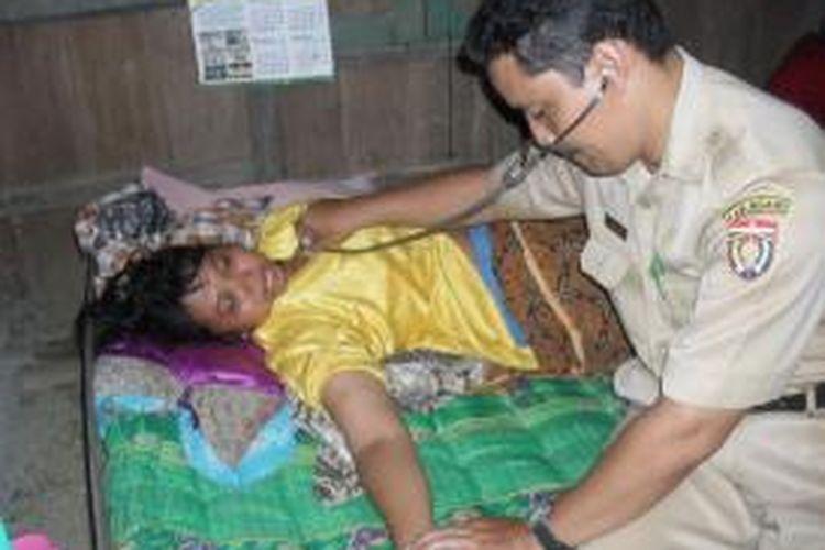 Seorang dokter Puskesmas Kasreman, Oong Murbiantoro memeriksa salah satu korban keracunan massal sekeluarga akibat mengkonsumsi telur rebus murah, Senin (28/4/2014).